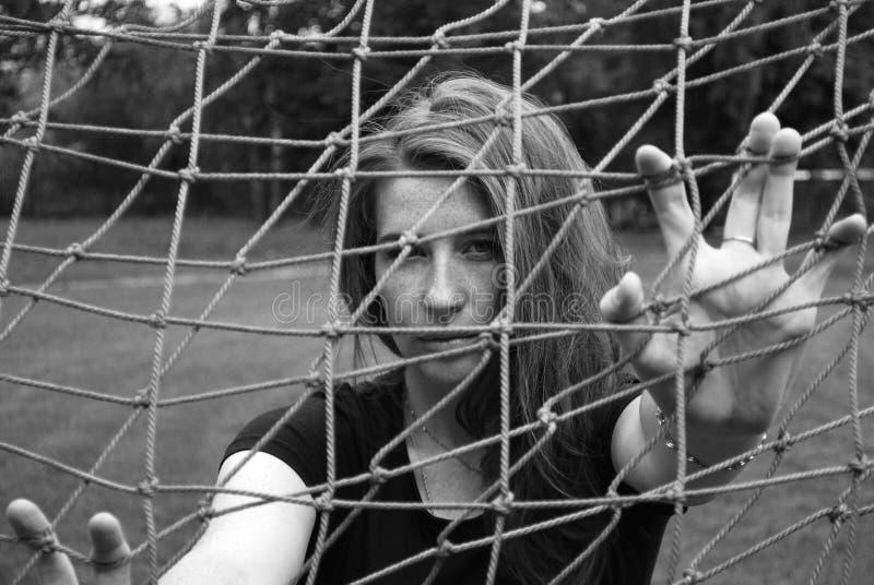 Молодая милая девушка смотря через сеть цели футбола r стоковое фото rf