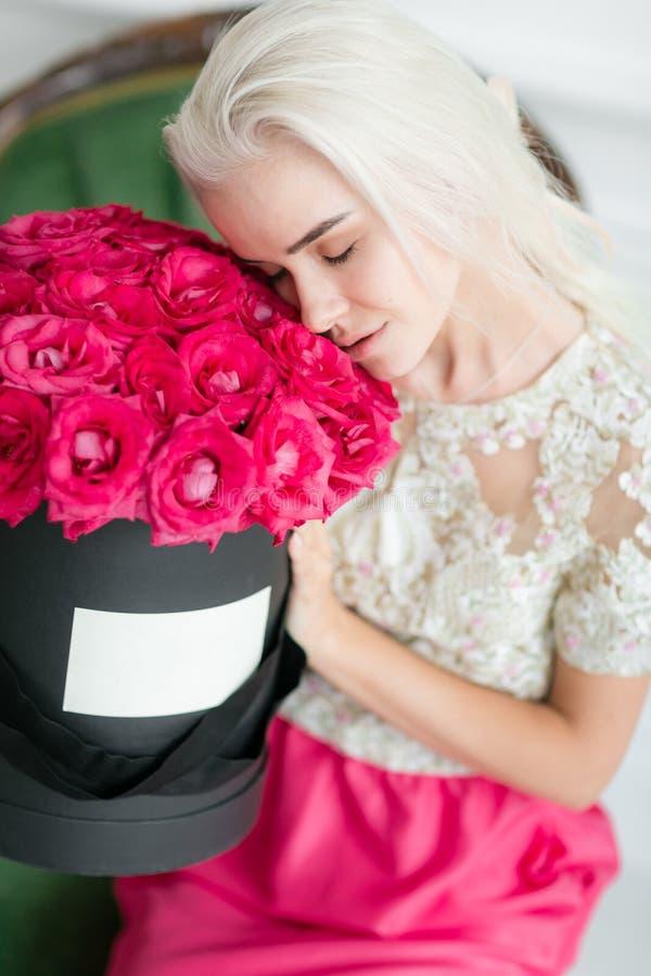 Молодая милая девушка с милой стороной и длинными светлыми волосами Женщина сидит и держащ черный ящик с розовыми розами античным стоковая фотография rf