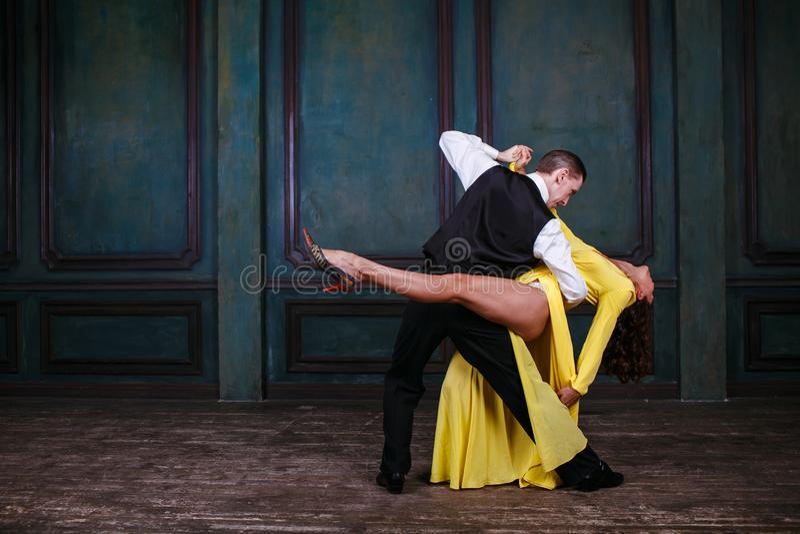 Молодая милая женщина в желтом платье и человек танцуют танго стоковая фотография rf