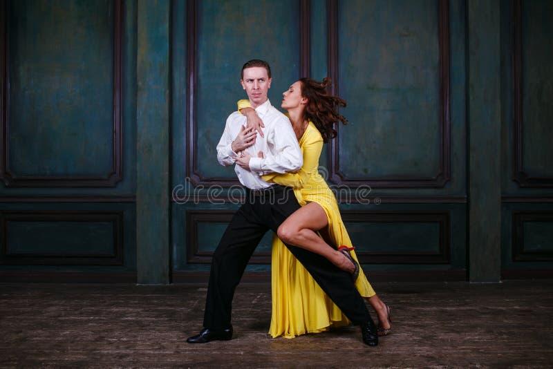 Молодая милая женщина в желтом платье и человек танцуют танго стоковые фотографии rf