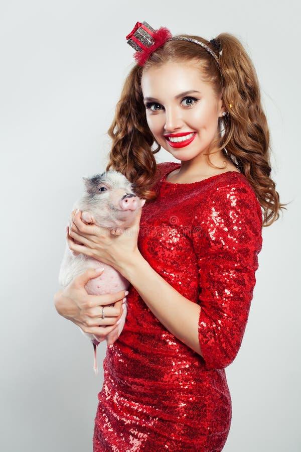 Молодая милая женщина в красном платье sequin держа меньшую свинью на белизне стоковое изображение rf