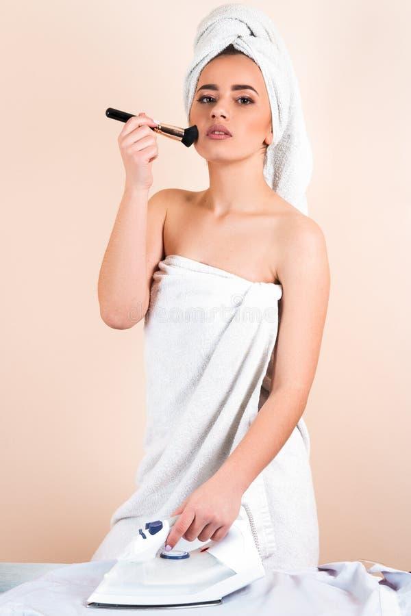 Молодая милая женщина в полотенце, утюжа, мать используя утюг на ironi стоковое фото