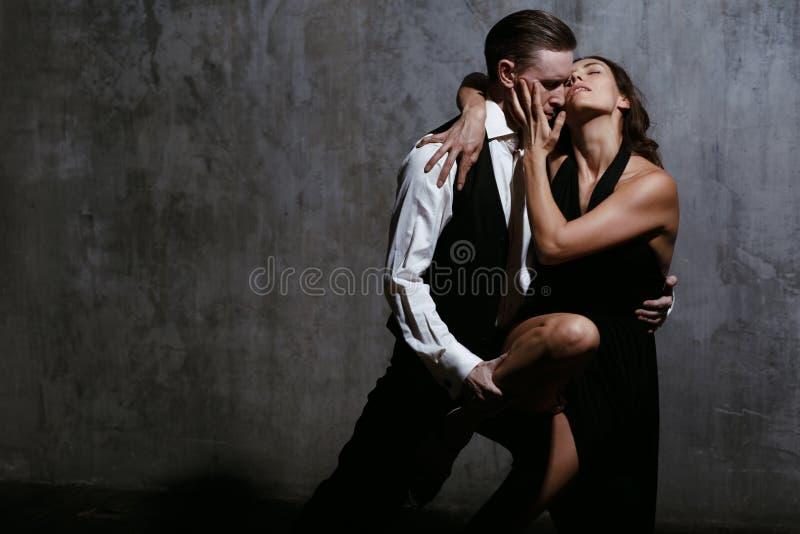 Молодая милая женщина в черном платье и человек танцуют танго стоковые фото