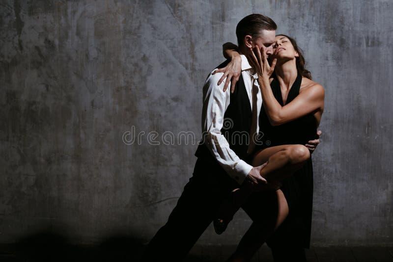 Молодая милая женщина в черном платье и человек танцуют танго стоковые изображения
