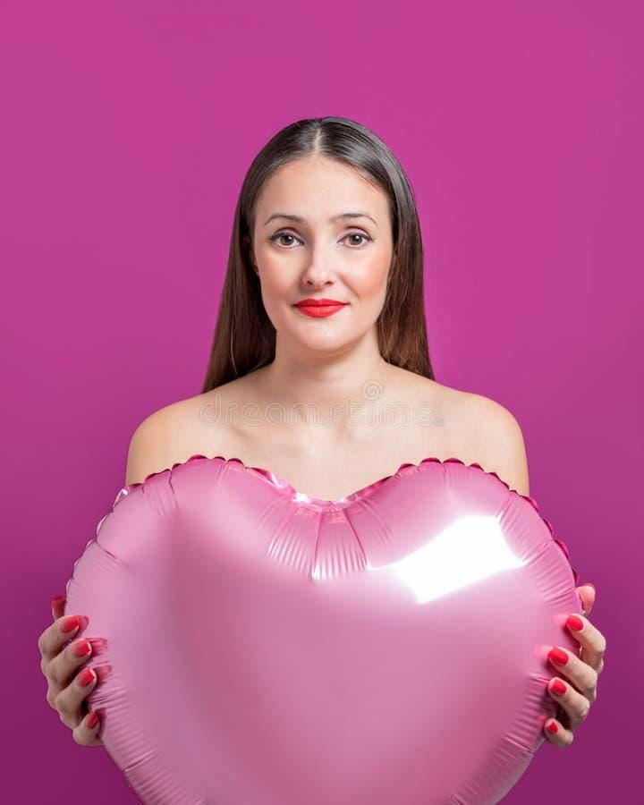 Молодая милая женщина держа воздушный шар сердца форменный Принципиальная схема дня ` s Валентайн стоковые изображения rf