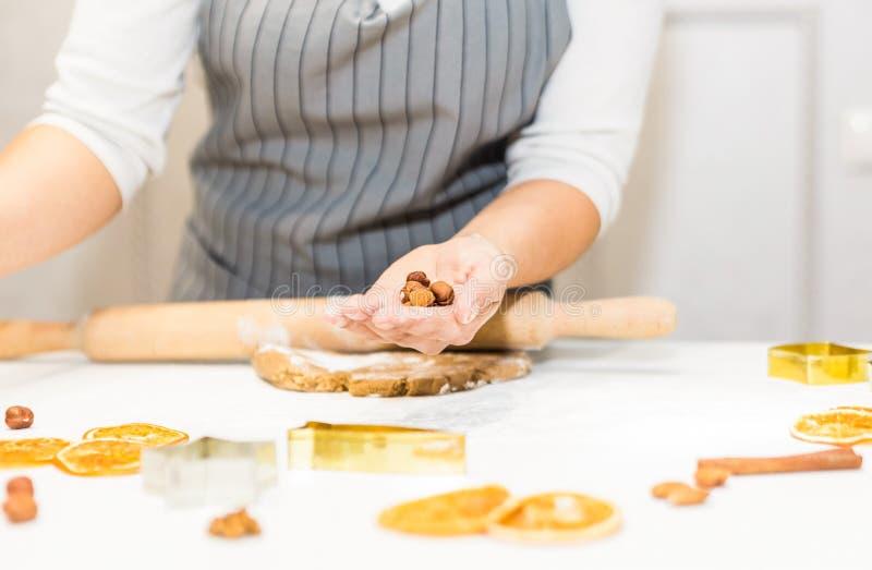Молодая милая женщина подготавливает тесто и печет пряник и печенья в кухне Веселое рождество и счастливое новое стоковое изображение rf
