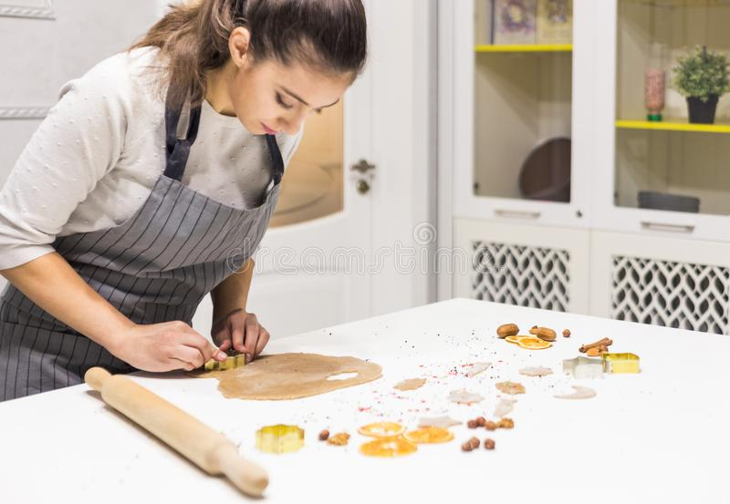 Молодая милая женщина подготавливает тесто и печет пряник и печенья в кухне Она делает форму звезды на стоковые изображения rf