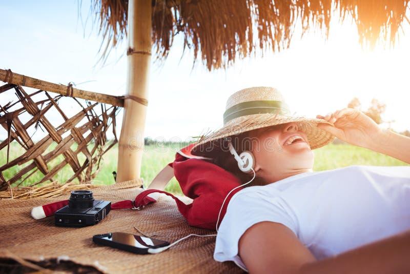 Молодая милая женщина при соломенная шляпа отдыхая outdoors и слушая музыка с наушниками на хорошем солнечном дне стоковые изображения