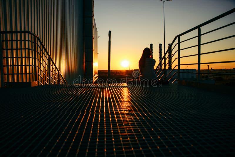 Молодая милая женщина сидя на лестницах мола стоковое изображение rf