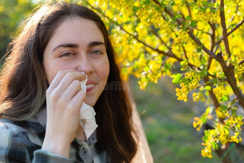 Молодая милая женщина усмехается и оконфужена ее аллергией для того чтобы зацвести цветень Концепция сезонных аллергий и холодов  стоковое изображение rf