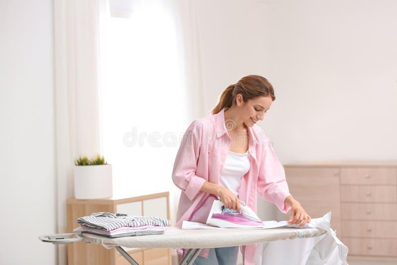 Молодая милая женщина утюжа чистую прачечную внутри помещения стоковые фотографии rf