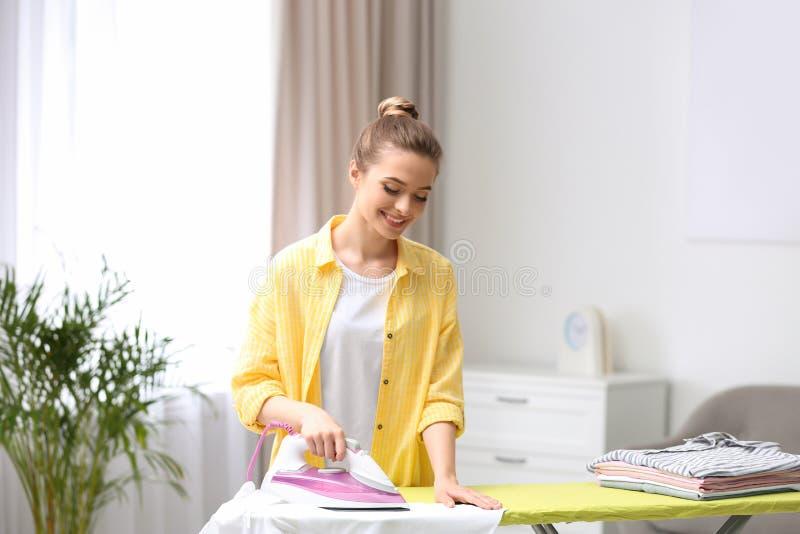 Молодая милая женщина утюжа чистую прачечную стоковые изображения rf