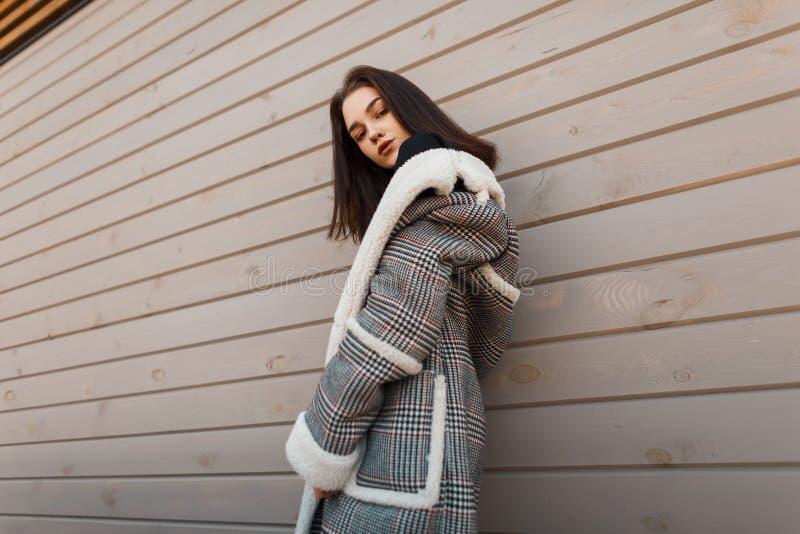 Молодая милая привлекательная женщина в роскошной checkered куртке с белым мехом в ретро стиле представляет на улице стоковые фотографии rf