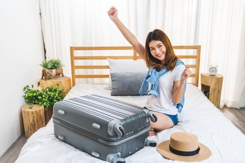 Молодая милая счастливая азиатская девушка закончила упаковать багаж чемодана на кровати в спальне, готовой для того чтобы свалив стоковое изображение rf
