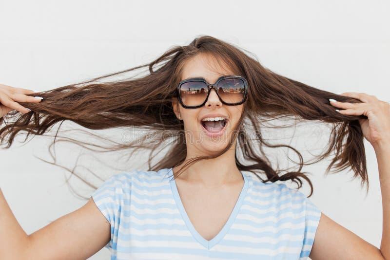 Молодая милая тонкая темн-с волосами девушка, нося случайные одежды, смотрит камеру и держит ее волосы стоковая фотография