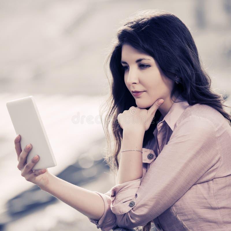 Молодая модельная женщина, использующая цифровой планшетный компьютер на открытом воздухе стоковые изображения