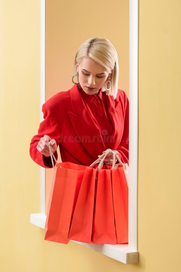 молодая модная женщина в красной одежде смотря в красные хозяйственные сумки стоковая фотография
