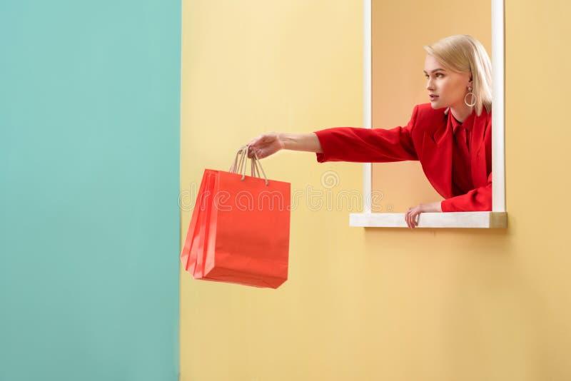 молодая модная женщина в красной одежде с красными хозяйственными сумками смотря вне стоковые фото