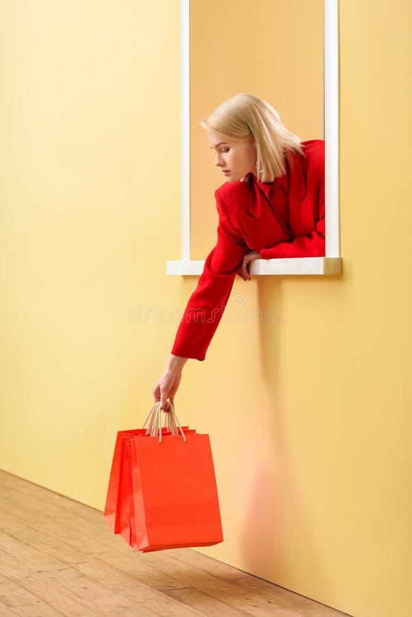 молодая модная женщина в красной одежде с красными хозяйственными сумками смотря вне стоковые изображения rf