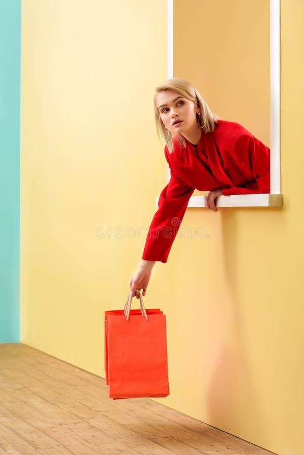 молодая модная женщина в красной одежде с красными хозяйственными сумками смотря вне стоковое фото rf