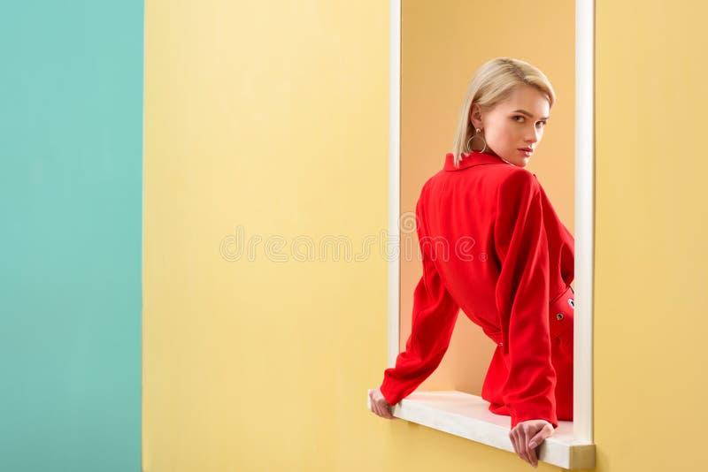 молодая модная женщина в красном костюме смотря вне стоковые фотографии rf