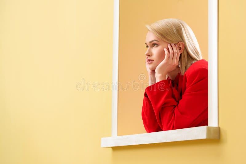 молодая модная женщина в красном костюме смотря вне стоковое изображение