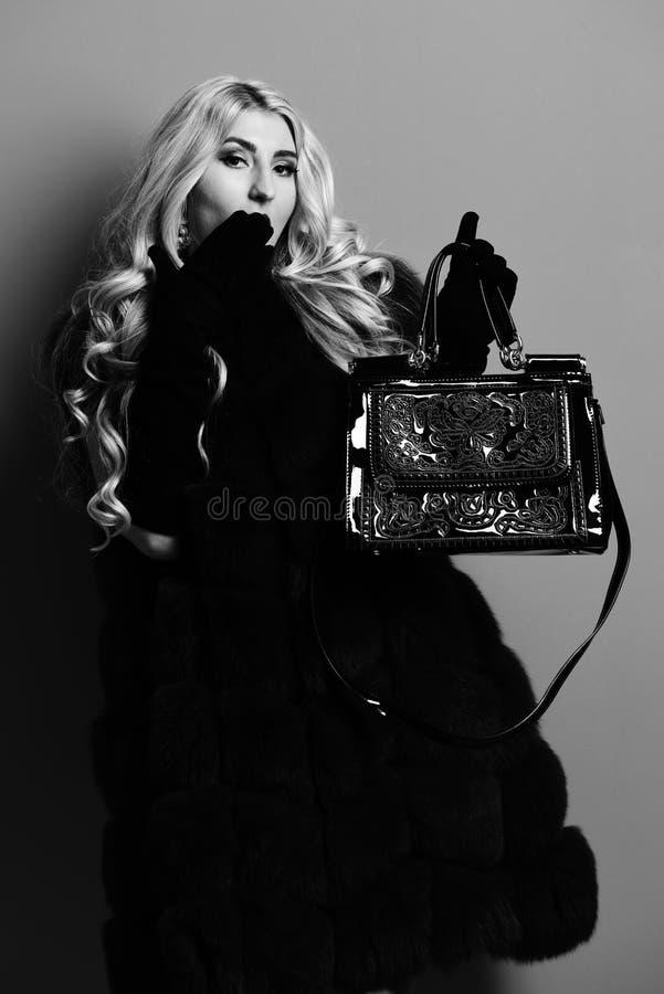 Молодая модная сексуальная милая женщина с красивыми длинными курчавыми белокурыми волосами в пальто талии бургундского меха и че стоковое фото
