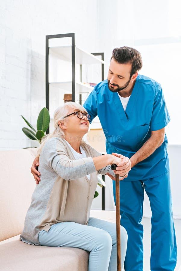 молодая мужская медсестра поддерживая старшую женщину стоковое фото
