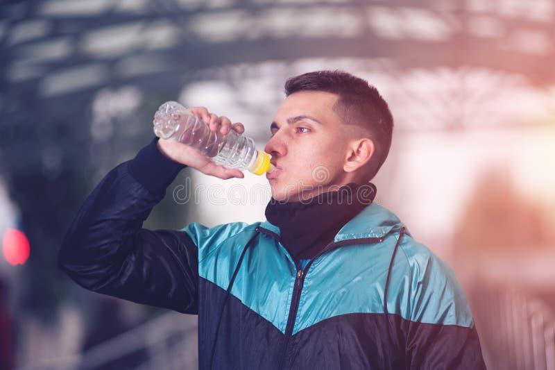 Молодая мужская питьевая вода бегуна во время разминки стоковые фотографии rf