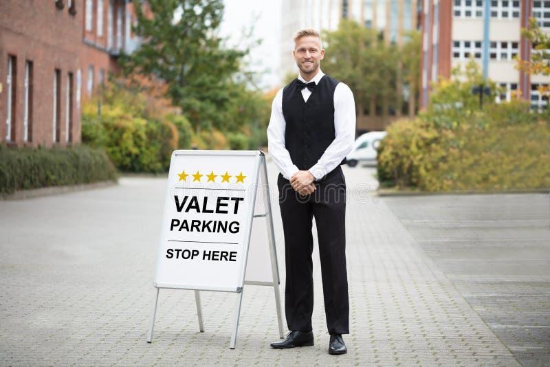 Молодая мужская слуга стоя близко знак автостоянки слуги стоковые фото