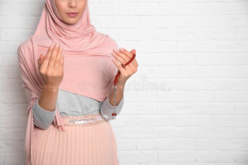 Молодая мусульманская женщина моля против кирпичной стены, крупного плана стоковое фото rf
