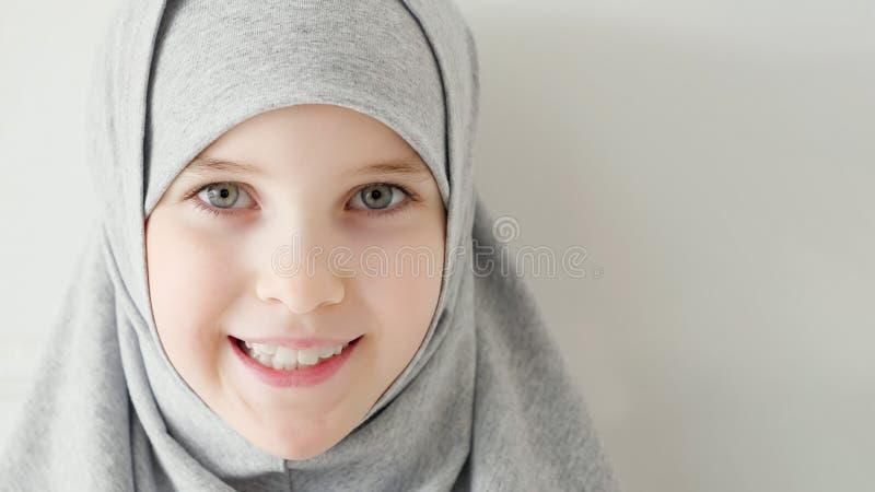 Молодая мусульманская предназначенная для подростков девушка в hijab застенчиво смотря камеру и усмехаться стоковое фото rf