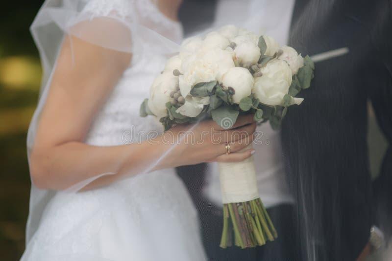 Молодая невеста в красивой белой стойке платья свадьбы около стены Она держит букет цветков в руках стоковое изображение