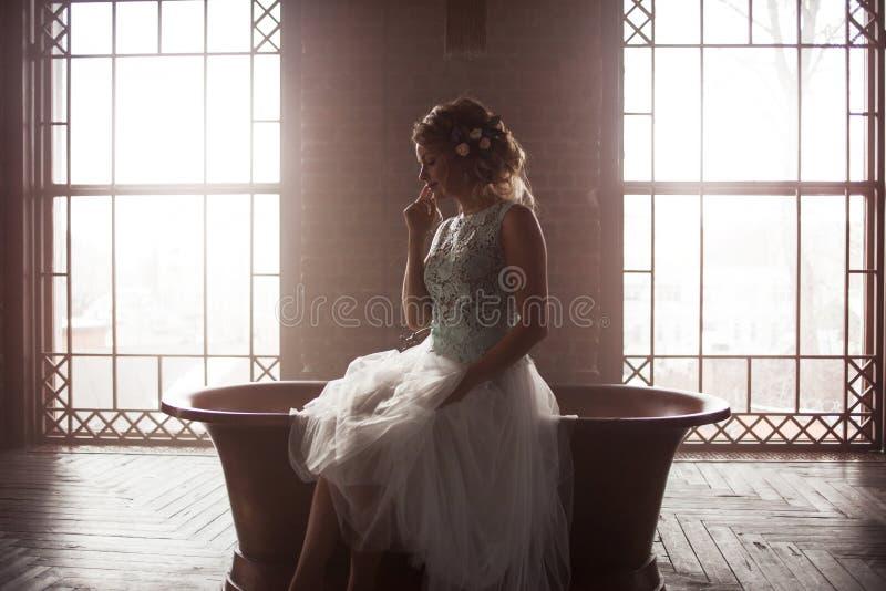 Молодая невеста в платье, силуэте на предпосылке окна сидит против света стоковые фото