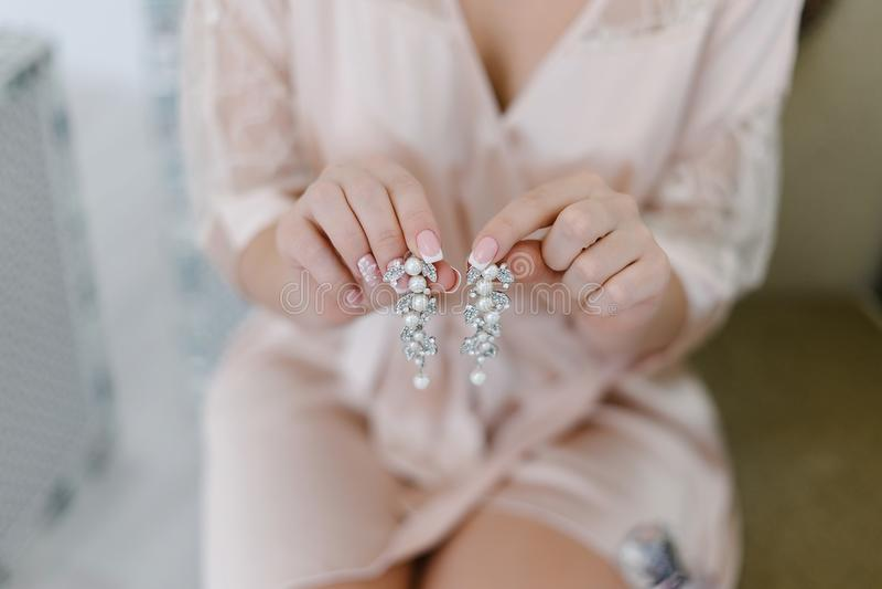 Молодая невеста держит серьги в ее руках стоковое изображение rf