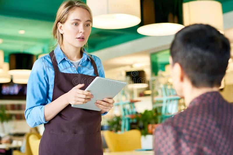 Молодая официантка принимая заказы в кафе стоковое изображение rf