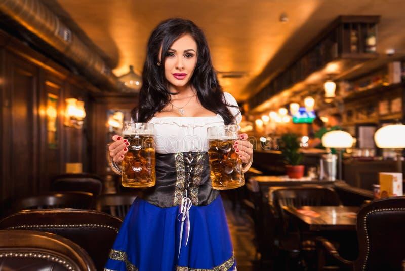 Молодая официантка приносит пиво к посетителям стоковая фотография