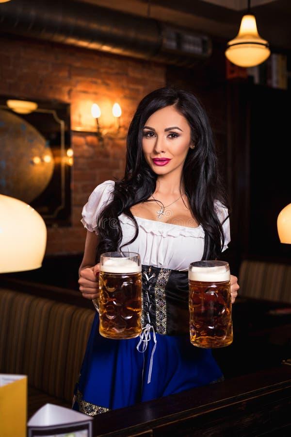 Молодая официантка приносит пиво к посетителям стоковые изображения