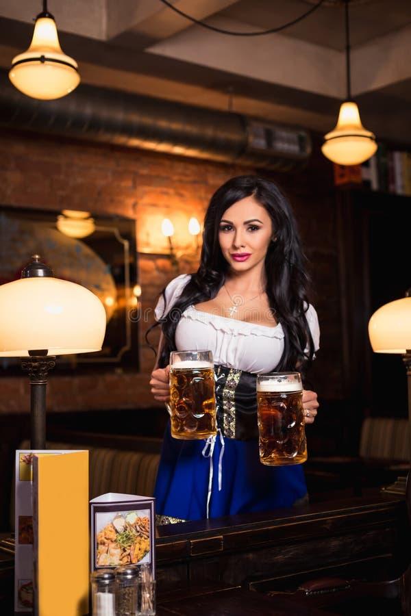 Молодая официантка приносит пиво к посетителям стоковые фото