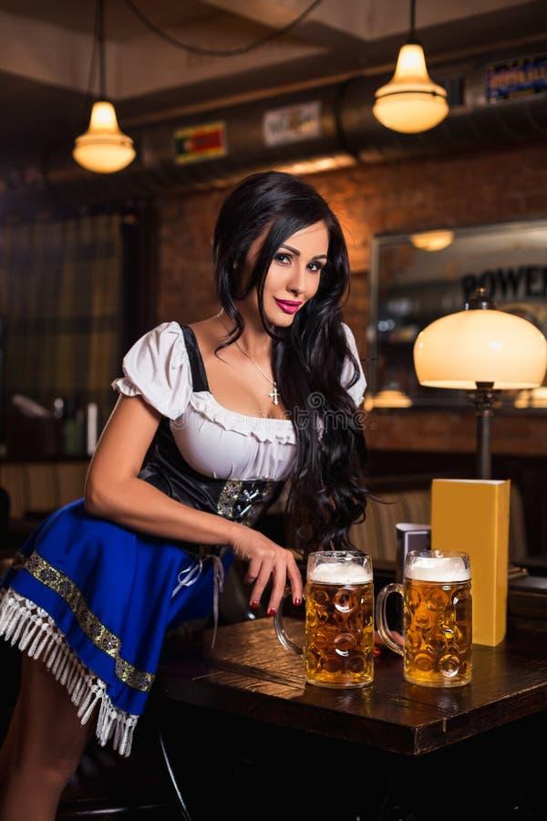 Молодая официантка приносит пиво к посетителям стоковое изображение