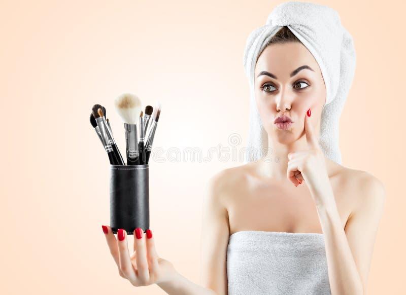 Молодая очаровательная девушка с белым полотенцем на ее голове держит a стоковая фотография