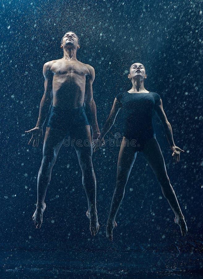 Молодая пара артистов балета танцуя rwater unde падает стоковое изображение