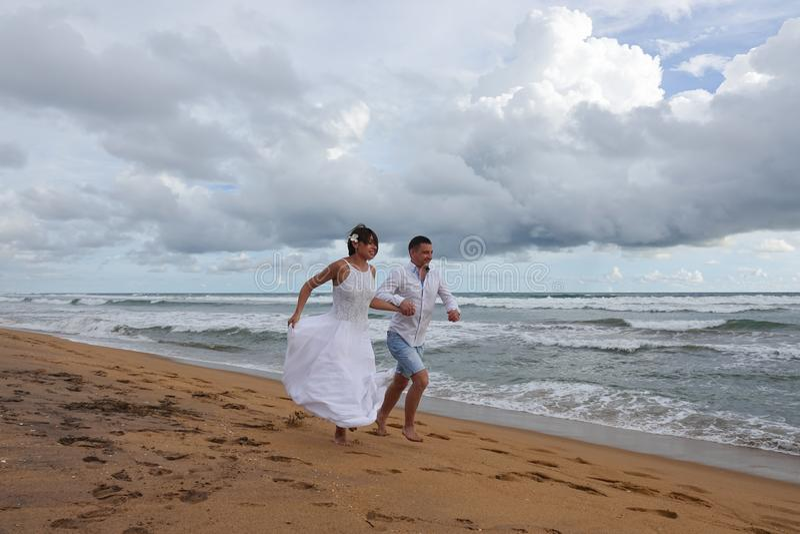 Молодая пара бежала по тропическому пляжу, держась за руки стоковое изображение rf