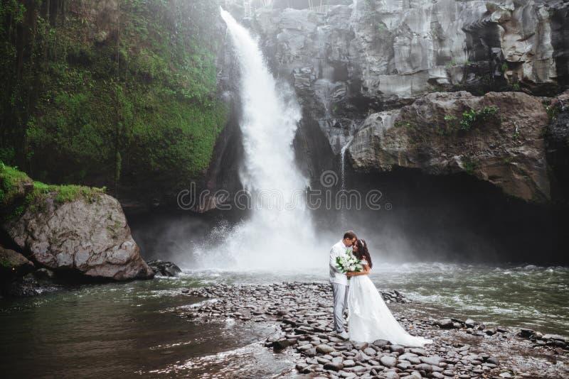 Молодая пара влюблена в жениха и невесту, день свадьбы у водопада горы стоковое фото rf