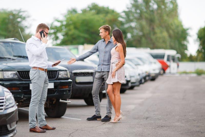 Молодая пара выбирает подержанный автомобиль Тема подержанного автомобиля стоковое изображение rf