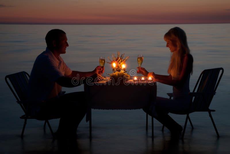 Молодая пара делит романтичный обедающий с свечками на пляже стоковые изображения