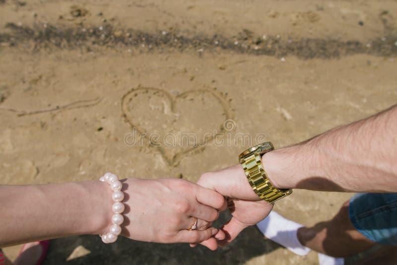 Молодая пара держит руки рекой В песке, сердце нарисовано стоковые изображения rf