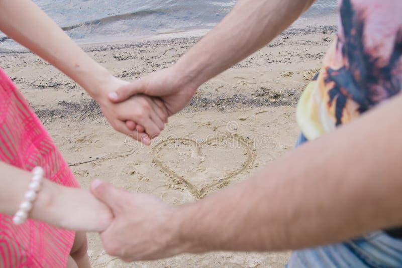 Молодая пара держит руки рекой В песке, сердце нарисовано стоковое изображение
