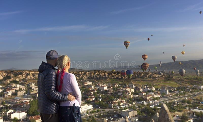 Молодая пара наблюдает, как множества воздушные шары летают над долинами в Cappadocia стоковые фото