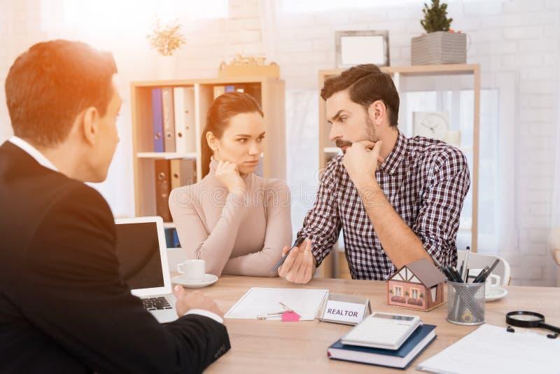 Молодая пара принимает решениея относительно приобретения дома сидя в офисе имущественного агентства недвижимости стоковые фотографии rf